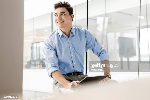 portrait of smiling young businessman with tablet at the window in office - rolled up sleeves stock pictures, royalty-free photos & images