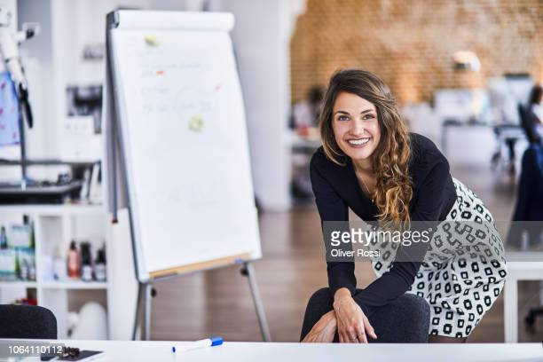 portrait of smiling young businesswoman in office - weibliche angestellte stock-fotos und bilder