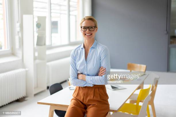 portrait of smiling young businesswoman in office - blouse stock pictures, royalty-free photos & images