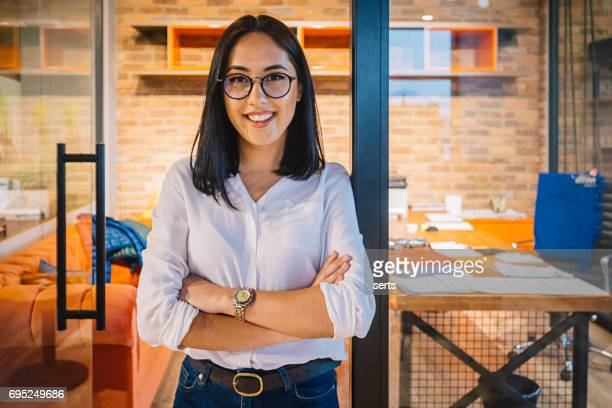 portrait of smiling young businesswoman in office - expertise stock pictures, royalty-free photos & images