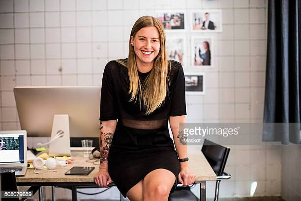 Portrait of smiling young businesswoman leaning at table in new office