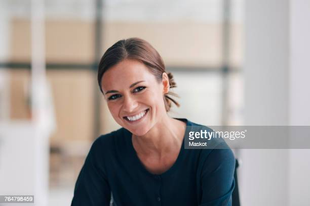 Portrait of smiling young businesswoman sitting at office