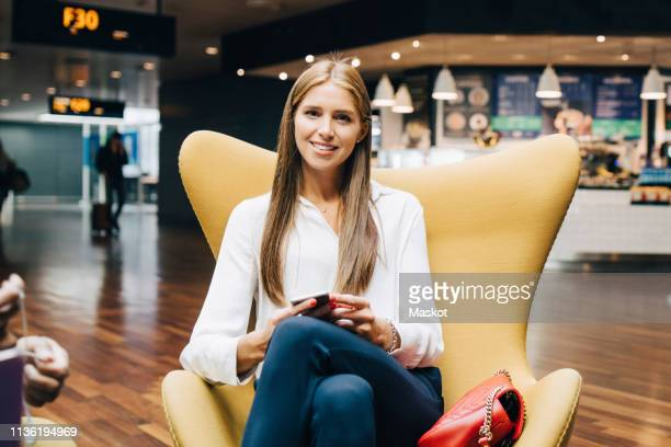 portrait of smiling young businesswoman sitting with smart phone in lobby at airport - gate fotografías e imágenes de stock