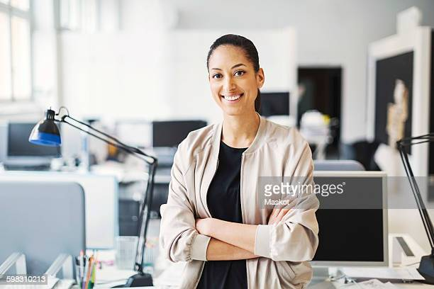 Portrait of smiling young businesswoman standing arms crossed in office