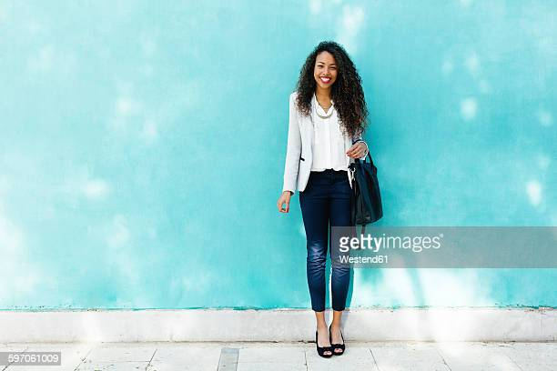 Portrait of smiling young businesswoman with leather bag standing in front of a blue wall