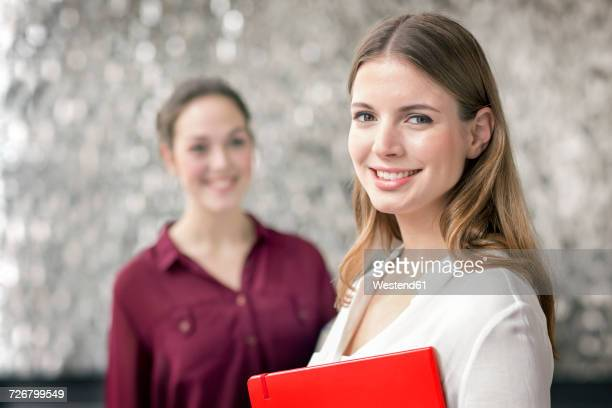 Portrait of smiling young businesswoman with notebook and colleague in the background