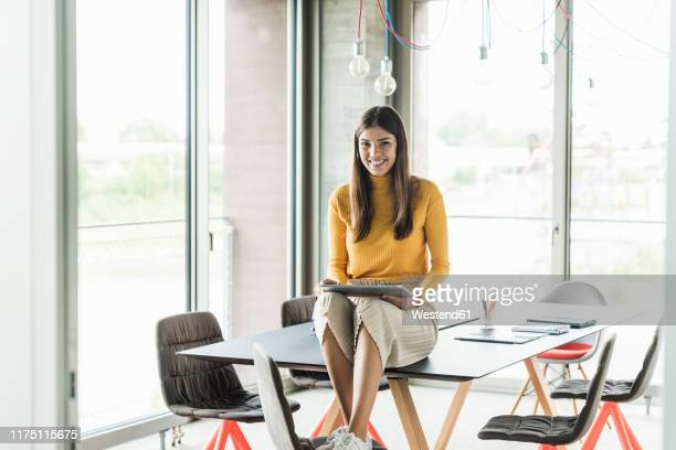 portrait of smiling young businesswoman with tablet in office - weibliche angestellte stock-fotos und bilder