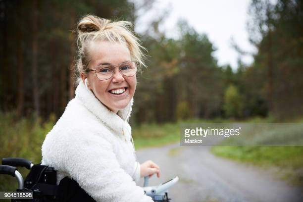 portrait of smiling young disabled woman sitting in wheelchair on road - autism spectrum disorder stock photos and pictures
