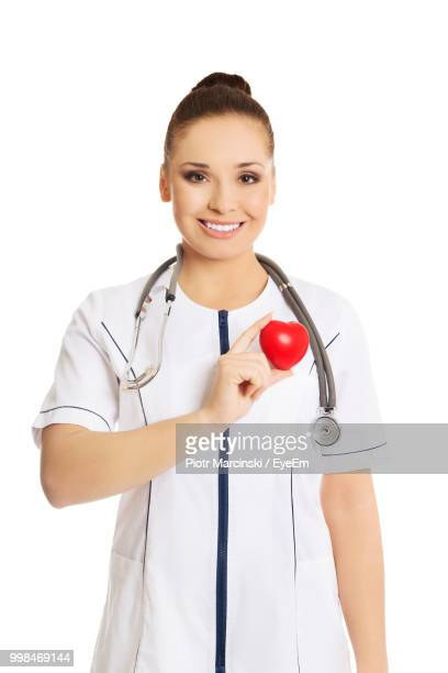 Portrait Of Smiling Young Doctor Holding Heart Shaped Stress Ball Against White Background