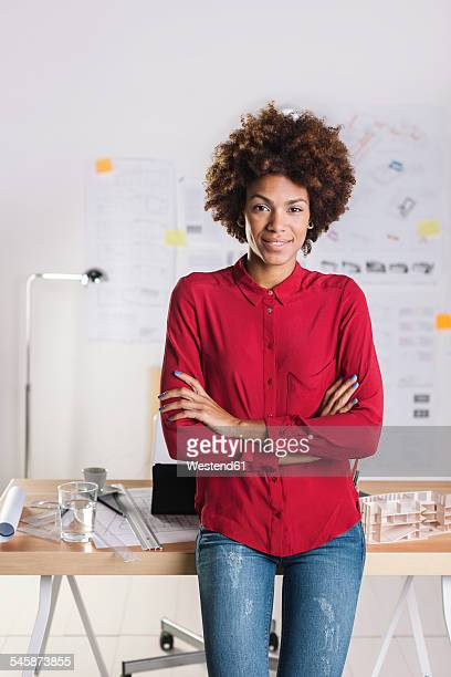Portrait of smiling young female architect with crossed arms standing at her office