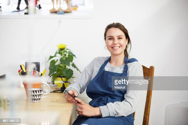 portrait of smiling young female engineer with smart phone sitting at table in workshop - inventor stock pictures, royalty-free photos & images