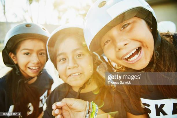 portrait of smiling young female friends making faces during skateboarding camp - sports training camp stock pictures, royalty-free photos & images
