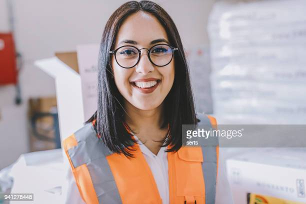 portrait of smiling young female industrial worker in office - reflective clothing stock pictures, royalty-free photos & images