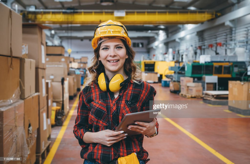 Portrait of smiling young female industry worker using digital tablet : Stock Photo