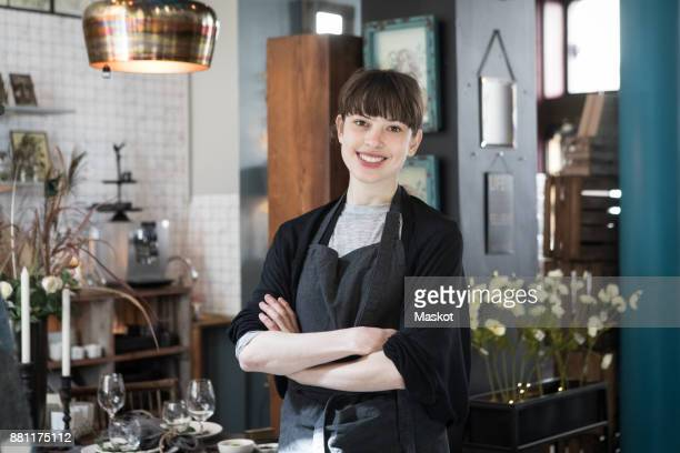 Portrait of smiling young female owner standing with arms crossed at store