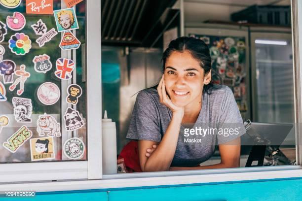 portrait of smiling young female saleswoman leaning on food truck window - food truck stock pictures, royalty-free photos & images