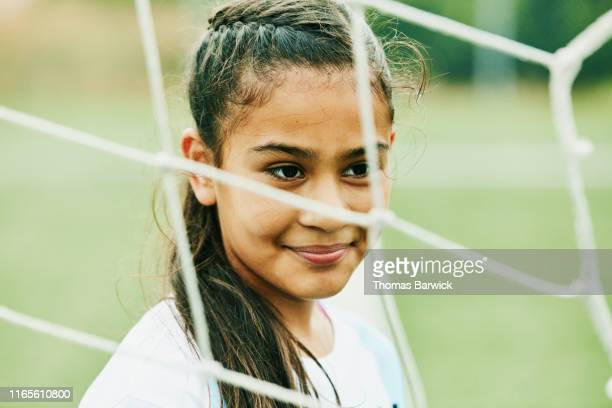 portrait of smiling young female soccer player standing in front of goal - football bulge stock pictures, royalty-free photos & images