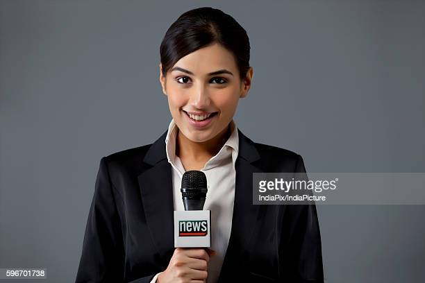 Portrait of smiling young female TV reporter against colored background