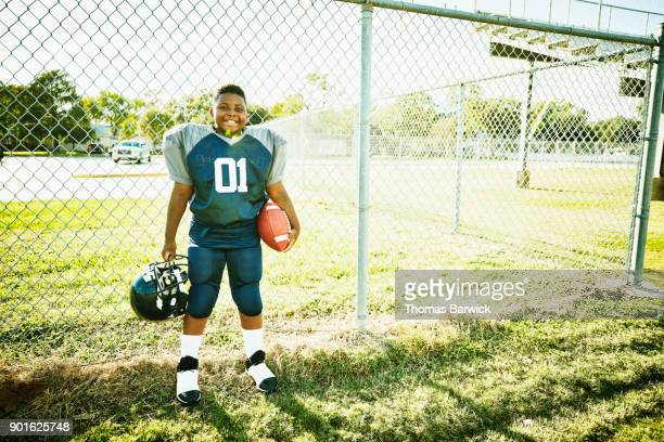 portrait of smiling young football player before football game - american football strip stock pictures, royalty-free photos & images