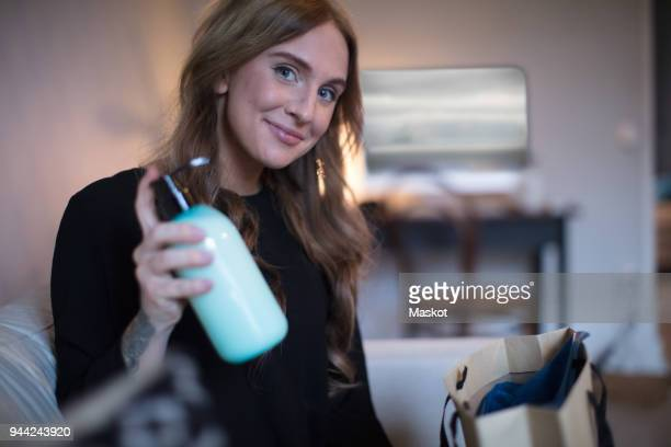 portrait of smiling young freelance worker holding soap dispenser at home - influencer stock pictures, royalty-free photos & images
