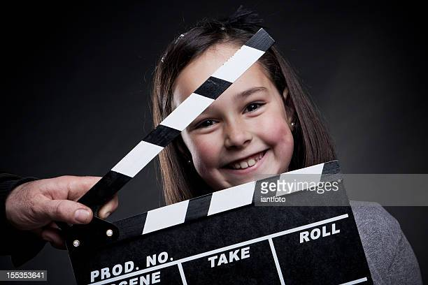 Portrait of smiling young girl behind a movie clapper board