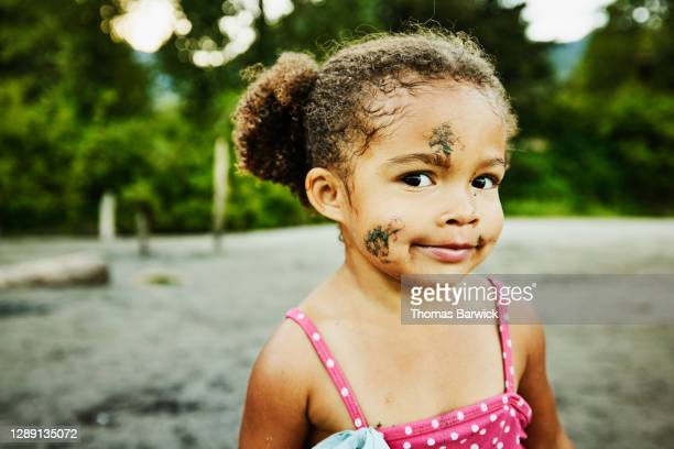 portrait of smiling young girl with sand on face standing on beach - naughty america stock pictures, royalty-free photos & images