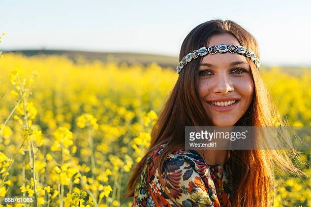 portrait of smiling young hippie in a rape field - hippie woman stock photos and pictures