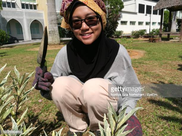 Portrait Of Smiling Young Holding Gardening Equipment At Lawn On Sunny Day