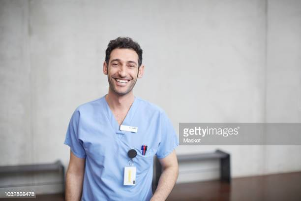 portrait of smiling young male nurse in blue scrubs standing against wall at hospital - nurse - fotografias e filmes do acervo