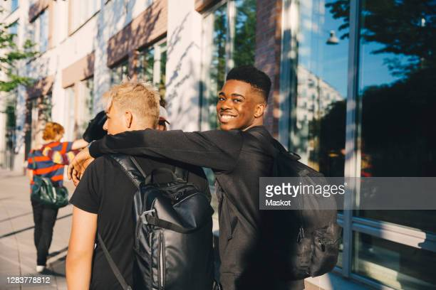 portrait of smiling young male with friend walking in city - looking over shoulder stock pictures, royalty-free photos & images