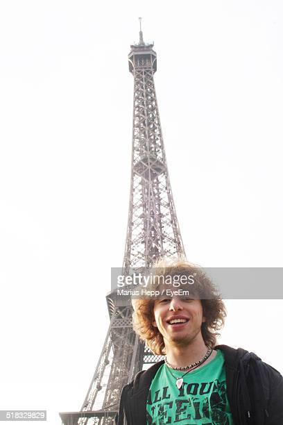 Portrait Of Smiling Young Man Against Eiffel Tower