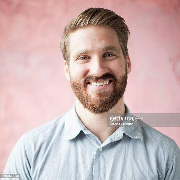 Portrait of smiling young man against pin background