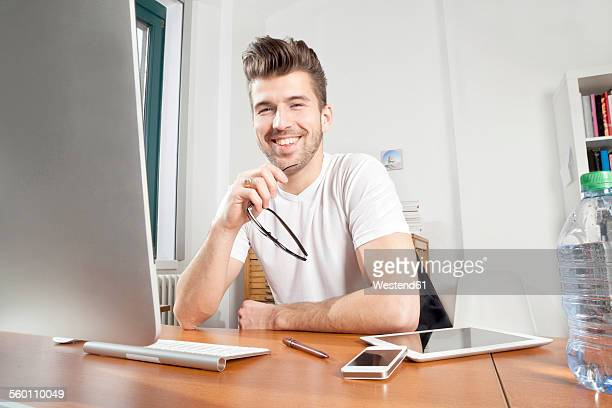 portrait of smiling young man at desk in an office - ポンパドール ストックフォトと画像
