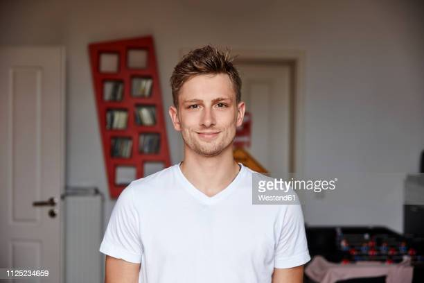 portrait of smiling young man at home - europese etniciteit stockfoto's en -beelden
