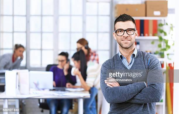 Retrato de sonriente hombre joven en la oficina