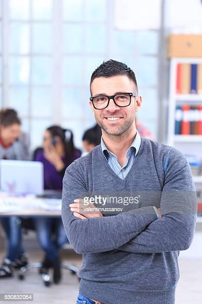 Portrait de souriant jeune homme au bureau-vertical