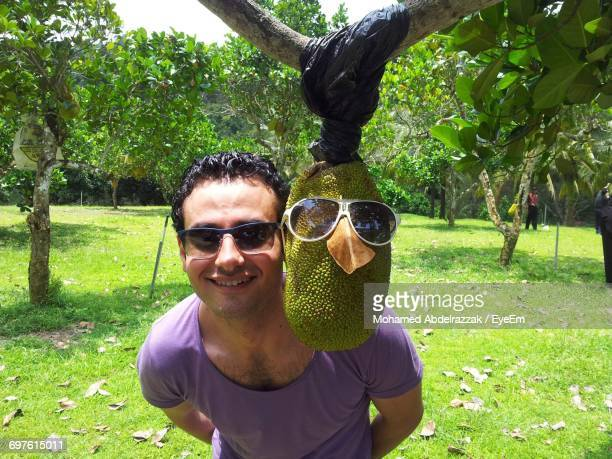 Portrait Of Smiling Young Man By Jackfruit Hanging From Branch At Park