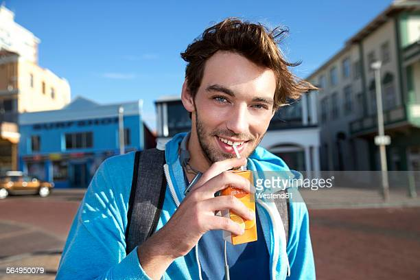 portrait of smiling young man drinking from juice box - juice carton stock photos and pictures