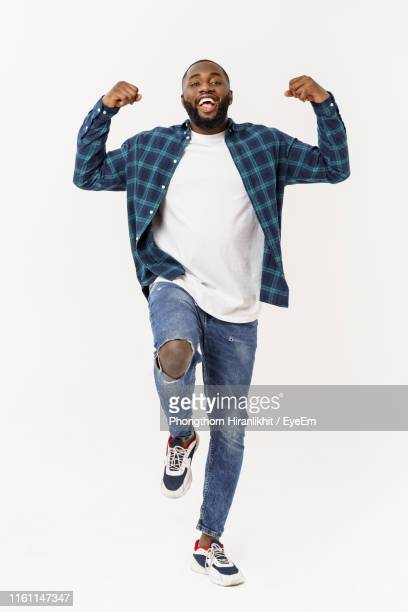 portrait of smiling young man gesturing while standing against white background - encuadre de cuerpo entero fotografías e imágenes de stock