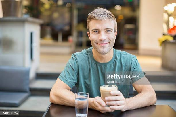 Portrait of smiling young man having coffee in restaurant