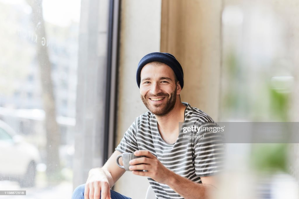 Portrait of smiling young man holding coffee cup at the window : Stock-Foto