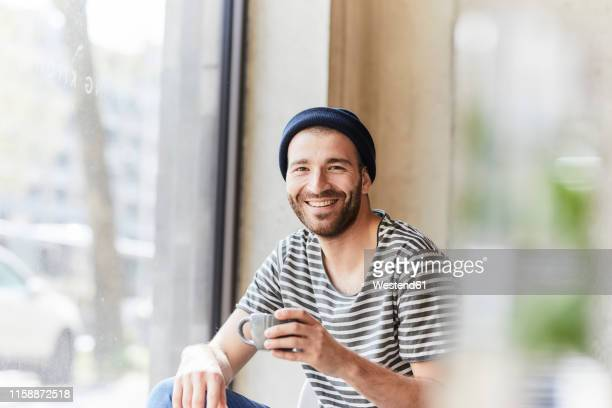 portrait of smiling young man holding coffee cup at the window - kaffee getränk stock-fotos und bilder