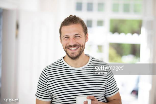 portrait of smiling young man holding cup of coffee at home - alleen één jonge man stockfoto's en -beelden