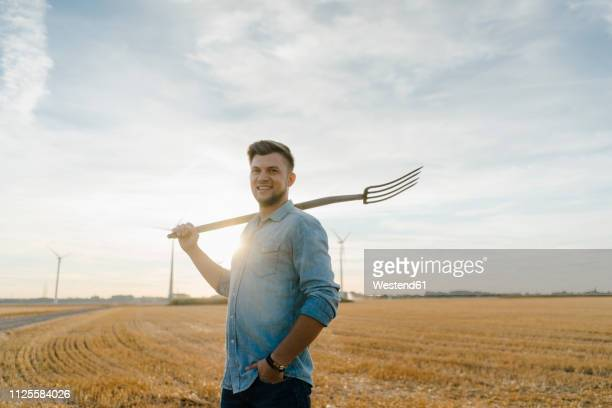 portrait of smiling young man holding pitchfork standing on stubble field - farmer stock pictures, royalty-free photos & images