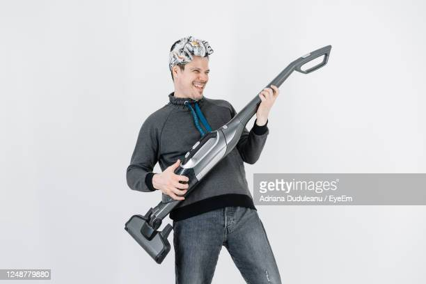 portrait of smiling young man holding vacuum cleaner against white background - modern rock stock pictures, royalty-free photos & images