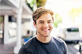 Portrait of smiling young man in city on sunny day