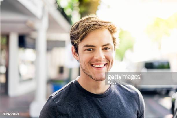 portrait of smiling young man in city on sunny day - men stock pictures, royalty-free photos & images