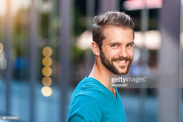 portrait of smiling young man in the city - tourner photos et images de collection