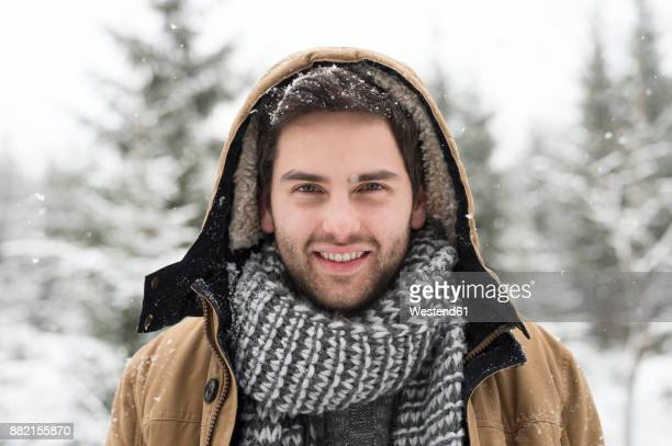 portrait of smiling young man in winter - hood clothing stock pictures, royalty-free photos & images