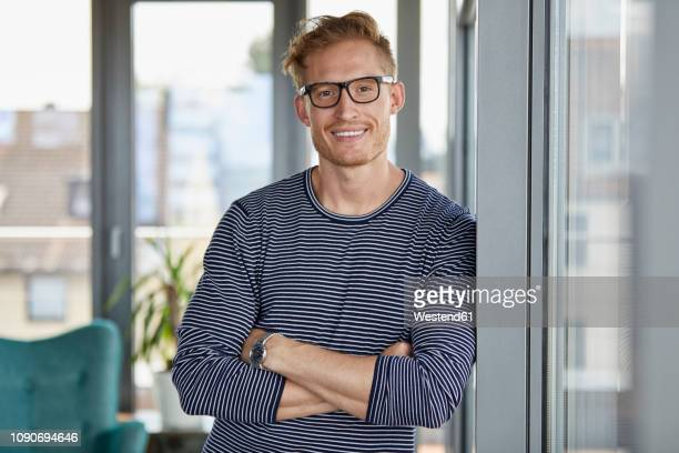 portrait of smiling young man leaning against window - arme verschränkt stock-fotos und bilder
